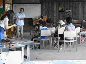 「エゾオオカミ物語」について、井上千代子の朗読と話を聞く子供たちと展示物を真剣に見る来場者